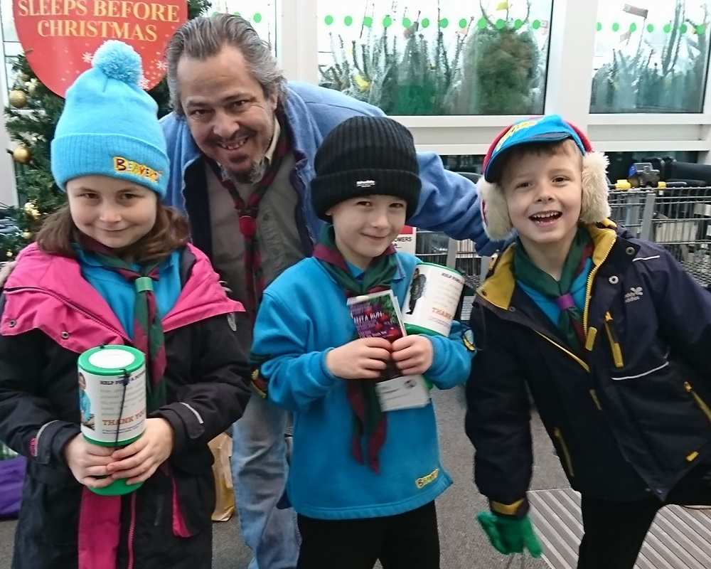 Three Beaver scouts fundraising with their leader.