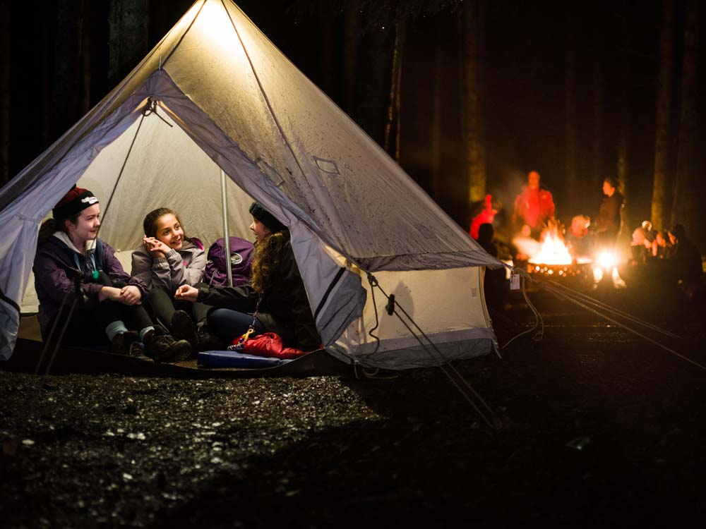 Three female Cub Scouts sit inside a bell tent with a group around a campfire visible in the background. The scene is set at night in a woodland.