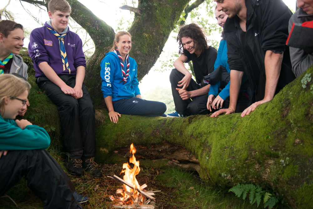 Helen Glover and a group of Scouts sit in a tree near a campfire.